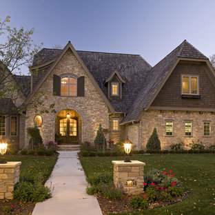 Example of a mid-sized classic two-story stone exterior home design in Minneapolis with a clipped gable roof