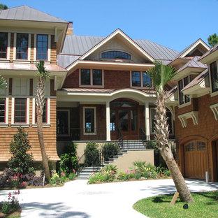 Diseño de fachada marrón, costera, extra grande, de tres plantas, con revestimiento de madera y tejado a doble faldón