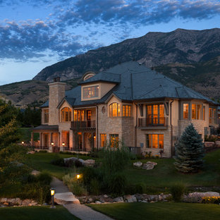 Inspiration for a timeless beige three-story stone exterior home remodel in Salt Lake City with a hip roof