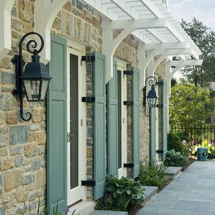 Esempio della facciata di una casa classica con rivestimento in pietra