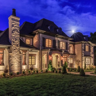 Inspiration for a huge mediterranean beige two-story stone house exterior remodel in Nashville with a gambrel roof and a shingle roof