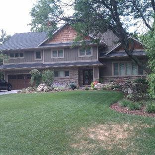 Imagen de fachada gris, de estilo americano, de tamaño medio, a niveles, con revestimientos combinados y tejado a dos aguas