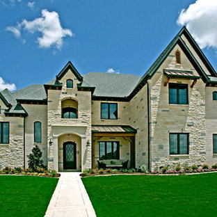 Example of a large trendy white two-story stone exterior home design in Dallas