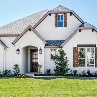 Mid-sized traditional white two-story brick exterior home idea in Dallas with a clipped gable roof