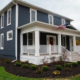 Aménagement d'une façade de maison bleue classique de taille moyenne et à un étage avec un revêtement en vinyle et un toit plat.