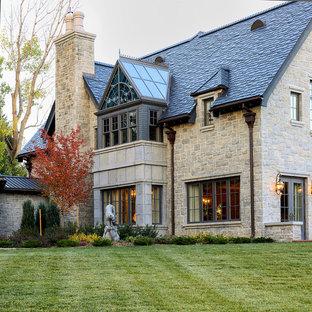 Ispirazione per la facciata di una casa ampia beige classica a due piani con rivestimento in pietra e tetto a capanna
