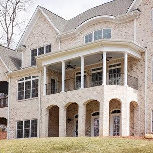 他の地域のトラディショナルスタイルのおしゃれな家の外観 (レンガサイディング、赤い外壁、半切妻屋根、戸建、板屋根) の写真