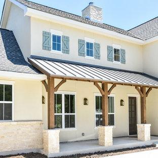 Imagen de fachada de casa beige, de estilo de casa de campo, grande, de dos plantas, con revestimiento de estuco, tejado a dos aguas y tejado de teja de madera