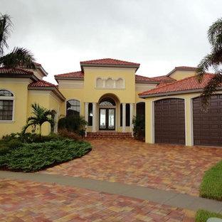 Imagen de fachada de casa amarilla, exótica, grande, de una planta, con revestimiento de estuco, tejado a cuatro aguas y tejado de teja de barro