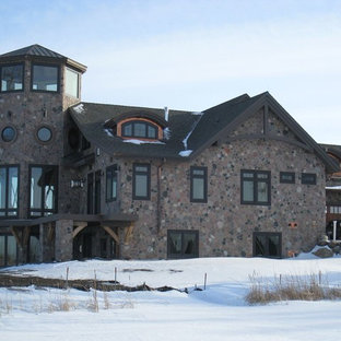 Example of a large trendy brown three-story stone gable roof design in Other
