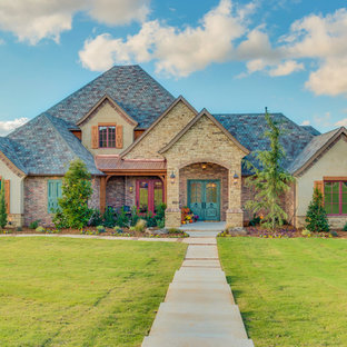 Large mountain style two-story brick exterior home photo in Oklahoma City with a hip roof