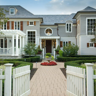 Design ideas for an expansive victorian house exterior in New York with three floors, wood cladding and a hip roof.