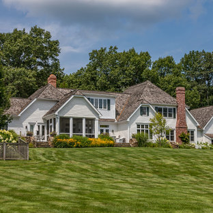 Elegant white two-story house exterior photo in New York with a clipped gable roof and a shingle roof