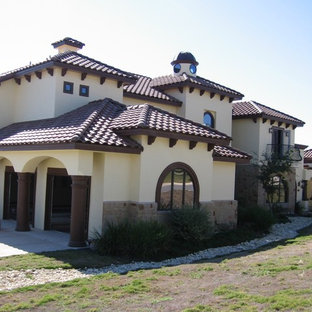 Large southwestern beige two-story stucco exterior home idea in Austin with a shed roof