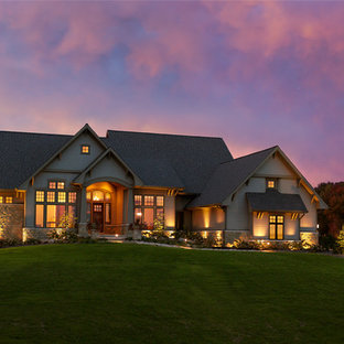 Large traditional beige one-story stone gable roof idea in Other