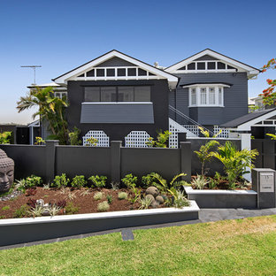 Photo of a large transitional two-storey black house exterior in Brisbane with wood siding and a gable roof.