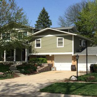 Modelo de fachada de casa verde, clásica renovada, de tamaño medio, a niveles, con revestimiento de aglomerado de cemento, tejado a dos aguas y tejado de teja de madera
