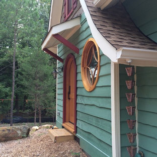 This is an example of a small eclectic two-storey green exterior in Raleigh with wood siding.