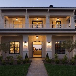 Idée de décoration pour une très grand façade de maison beige tradition à un étage avec un revêtement mixte, un toit à quatre pans et un toit en tuile.