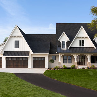 Elegant white two-story exterior home photo in Minneapolis with a mixed material roof