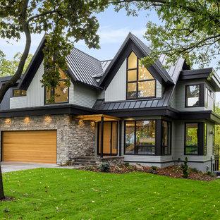 Immagine della villa grande grigia contemporanea a due piani con rivestimenti misti, tetto a capanna e copertura in metallo o lamiera