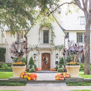 Diseño de fachada beige, tradicional, de tres plantas, con revestimiento de estuco y tejado a dos aguas