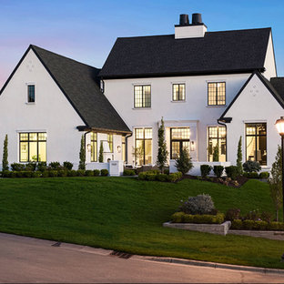 Large country white two-story stucco exterior home photo in Minneapolis with a shingle roof