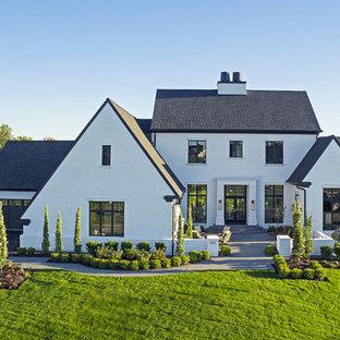 Modelo de fachada de casa blanca, campestre, grande, de dos plantas, con revestimiento de estuco, tejado a dos aguas y tejado de teja de madera