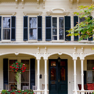 Ornate white three-story wood exterior home photo in New York