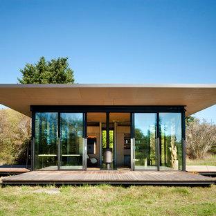 Esempio della facciata di una casa piccola moderna a un piano con rivestimento in legno e tetto piano