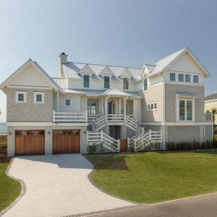 Пример оригинального дизайна: большой, трехэтажный, бежевый частный загородный дом в морском стиле с комбинированной облицовкой, двускатной крышей и металлической крышей