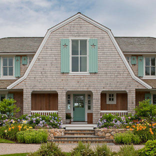 Example of a large classic beige two-story wood house exterior design in Boston with a gambrel roof and a shingle roof