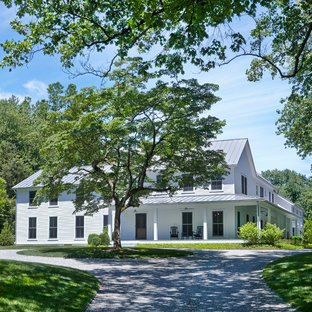 Large farmhouse white two-story exterior home photo in New York with a metal roof