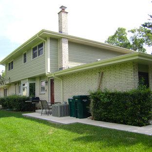 Modelo de fachada verde, de estilo de casa de campo, de tamaño medio, de dos plantas, con revestimientos combinados