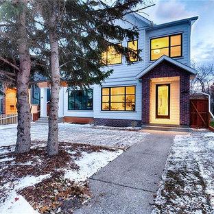 カルガリーのカントリー風おしゃれな家の外観 (コンクリート繊維板サイディング、切妻屋根、デュープレックス、板屋根) の写真