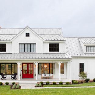 На фото: двухэтажный, белый, деревянный частный загородный дом в стиле кантри с двускатной крышей, металлической крышей и отделкой доской с нащельником с