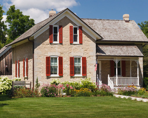 example of a mid sized country beige two story stone gable roof design in