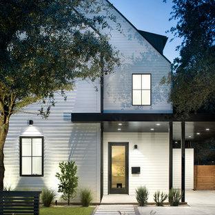 Aménagement d'une grand façade de maison blanche campagne à un étage avec un toit à deux pans et un toit mixte.
