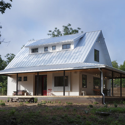 Example of a cottage wood exterior home design in Austin with a metal roof