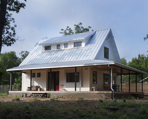 Example Of A Country Wood Exterior Home Design In Austin With A Metal Roof