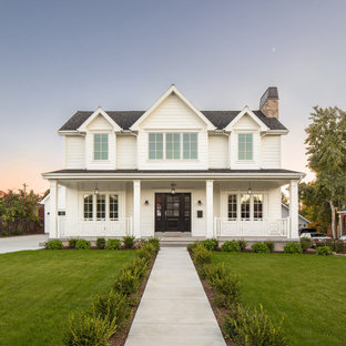 Immagine della facciata di una casa unifamiliare bianca country a due piani con tetto a capanna e copertura a scandole