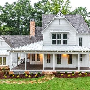 Ispirazione per la facciata di una casa unifamiliare grande bianca country a due piani con copertura a scandole, rivestimento in vinile e tetto a padiglione