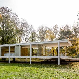 Imagen de fachada blanca, moderna, de una planta, con revestimiento de vidrio y tejado plano