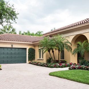 Inspiration for a mediterranean beige one-story house exterior remodel in Miami with a clipped gable roof