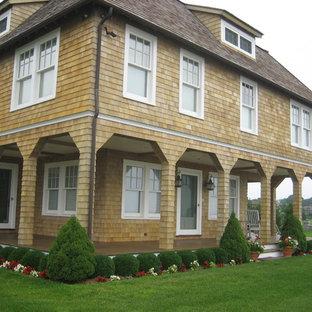 Diseño de fachada de casa beige, marinera, grande, de tres plantas, con revestimiento de madera, tejado a doble faldón y tejado de teja de madera