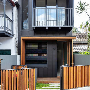 Photo of a mid-sized contemporary two-storey black house exterior in Sydney with metal siding.