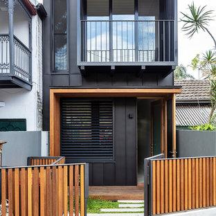 Modern inredning av ett mellanstort svart hus, med metallfasad och två våningar