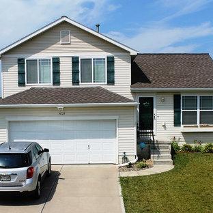 Ejemplo de fachada blanca, clásica, de tamaño medio, a niveles, con revestimiento de vinilo y tejado a dos aguas