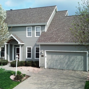 Example of a large classic gray two-story gable roof design in Omaha