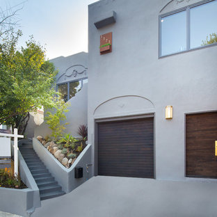 Foto de fachada de casa gris, mediterránea, pequeña, de dos plantas, con revestimiento de estuco y tejado plano
